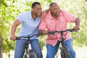 Two men on bikes outdoors smiling. Father and elderly son outdoors.