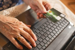 Close up of senior woman's hands with laptop computer and credit card.