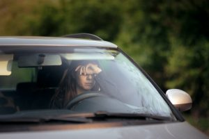 image of a woman looking stressed inside of a car